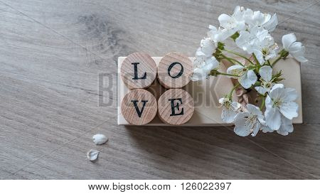 Closeup of love word on wooden table with fresh flowers ** Note: Shallow depth of field