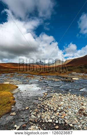 the mountain river against a glacier in the evening autumn colors