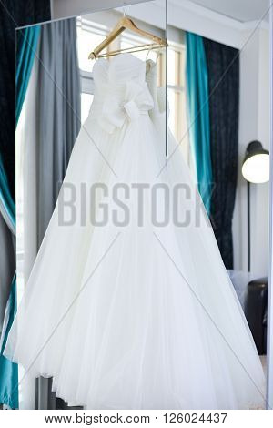 Wedding Dress Hanging On The Mirror