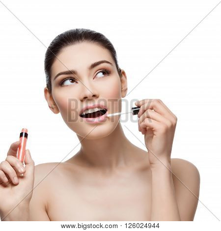 Beautiful young woman applying pink lipgloss to lips. Isolated over white background. Copy space. Square composition.
