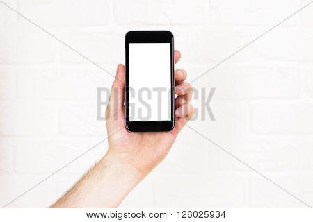 Male hand holding blank white smartphone on white brick background. Mock up