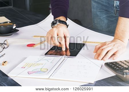 Male hands using tablet placed on wooden desktop with many different office tools and coffee