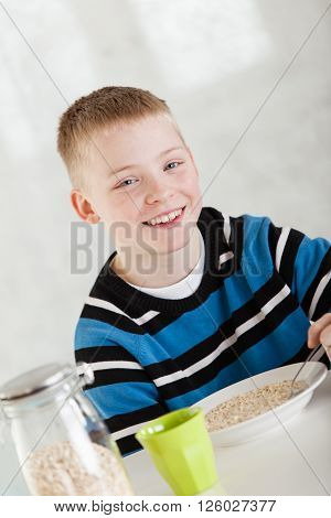Giggling Blond Child Eating Oatmeal In Bowl