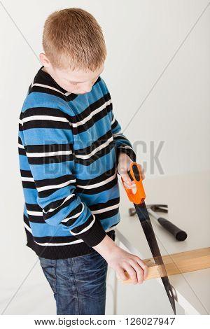 Boy Saws Through Piece Of Wood Near Hammer