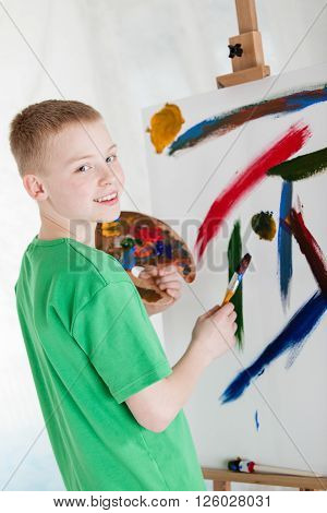 Young Artist Smiles Over His Shoulder Near Easel