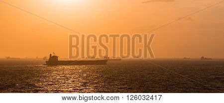 Fleet of cargo ship at anchorage while sunset.