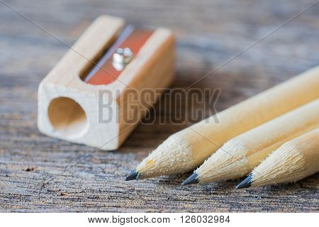 Wooden pencils with sharpening shavings on wooden table background.