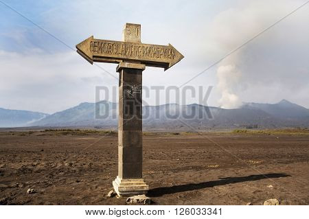 Signposts pointing to the bottom of the volcano caldera. Mt. Bromo volcano during sunrise the magnificent view of Mt. Bromo located in Bromo Tengger Semeru National Park East Java Indonesia.