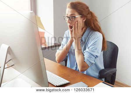 Young Redhead Female Student Wearing Glasses And Blue Shirt Looking Stressed And Terrified At The Sc