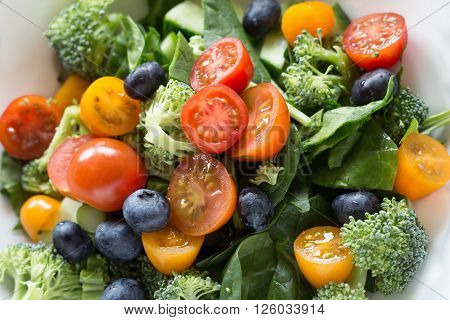 Fresh salad with tomatoes spinach blueberries broccoli and cucumber. Can be used for food healthy vegetarian vegetable and salad themes