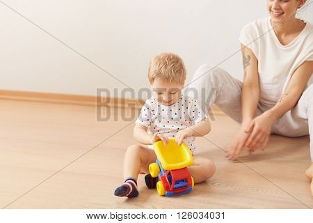 Portrait Of Lovely Infant Playing With Toy Truck Sitting On The Floor At Home With Interested Look W