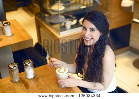 Overhead view of smiling brunette woman sitting in a bar with a Latte macchiato in front of her