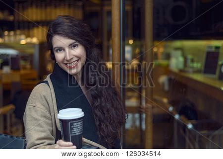 Young brunette woman in brown woollen jacket and scarf sipping coffee from cup near door of bistro
