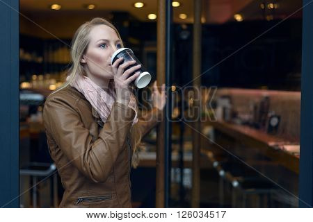 Young blond woman in brown leather jacket and scarf sipping coffee from cup near door of bistro