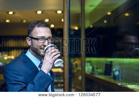 Middle-aged bearded man in blue business suit and necktie sipping coffee from cup near door of bistro