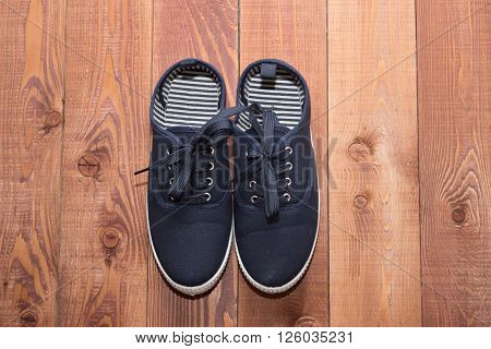 Pair Of Blue Running Shoes On A Wooden Floor Background