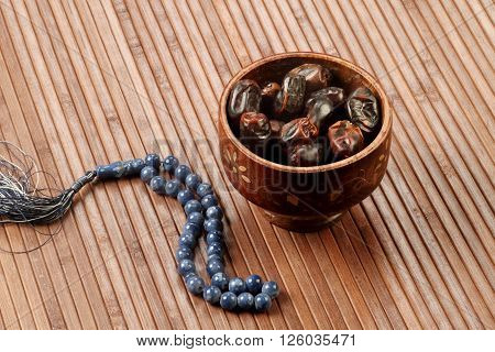 Ramadan Fresh dates in a wooden bowl with rosary