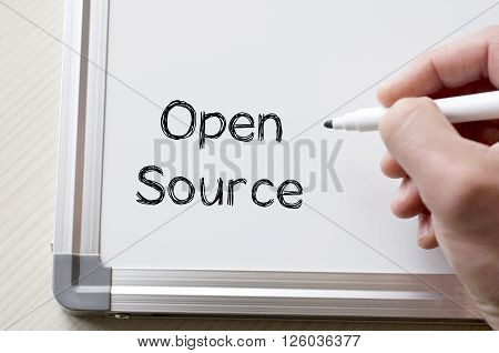 Human hand writing open source on whiteboard