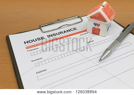 House Insurance application form with model house and pen