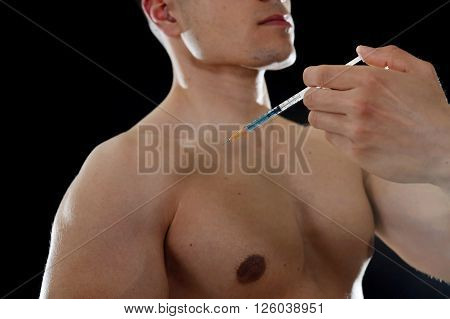 young body building sportsman using steroids for increasing sport and athletic performance injecting syringe in shoulder in sport cheat doping and illegal use of hormones