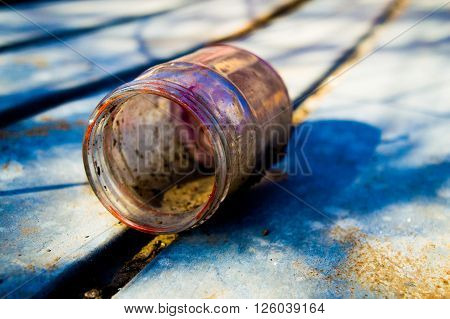 Colorful empty paint jar, on a rusted metal roof.