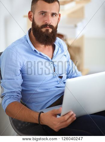 Handsome young man sitting and working on laptop computer