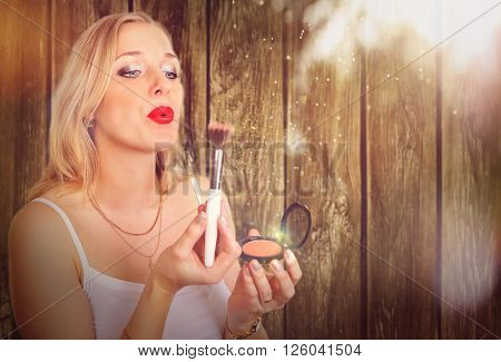 Portrait of beautiful woman model holding make-up brush with sparkle on the wood background