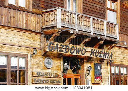 ZAKOPANE POLAND - MARCH 06 2016: Restaurant's name over the entrance to Gazdowo Kuznia located in wooden building which until 1898 was the biggest hotel in Zakopane nowadays it houses a restaurant