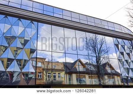 ZAKOPANE POLAND - MARCH 09 2016: Residential building and the shopping mall is reflected in the glass facade of another shopping mall at Krupowki street main shopping street in the city