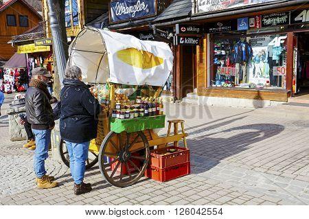 ZAKOPANE POLAND - MARCH 06 2016: Unidentified couple are buying Oscypek cheese at Krupowki street since February 02 2007 Oscypek is Polish regional product protected by EU law