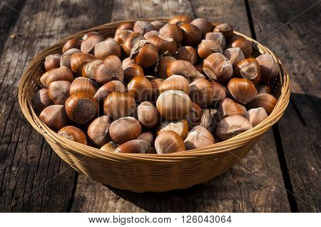 Full wooden basket with raw hazelnuts on the table