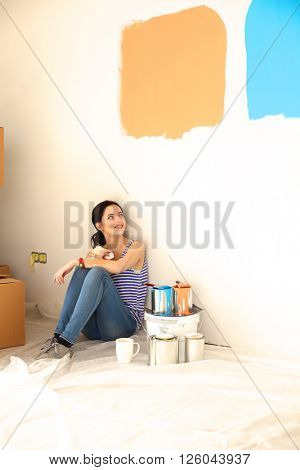 Woman choosing paint colour from swatch for new home sitting on