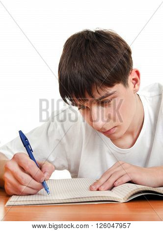 Teenager writing at the School Desk on the White Background