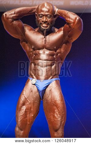MAASTRICHT THE NETHERLANDS - OCTOBER 25 2015: Male bodybuilder Elias Bogane flexes his muscles and shows his best physique in a abdominal and thighs pose on stage at the World Grandprix Bodybuilding and Fitness of the WBBF-WFF