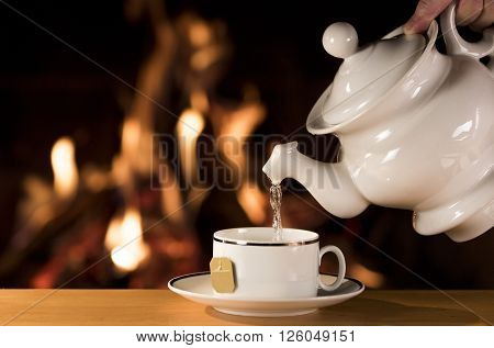 Cup of Tea / Water being poured into a cup of tea with a fireplace on the background