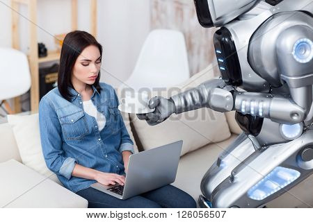 Out of temper. Modern big robot giving cup of coffee to a cheerless   attractive girl who is sitting on the couch and using laptop