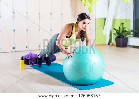 Fit woman doing push ups with medicine ball workout out arms Exercise training triceps and pectorals muscles.