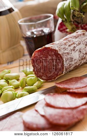 Close up of Italian salami with broad bean over a chopping board and a glass of red wine