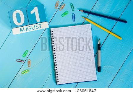 August 1st. Image of august 1 wooden color calendar on blue background. Summer day. Empty space for text.