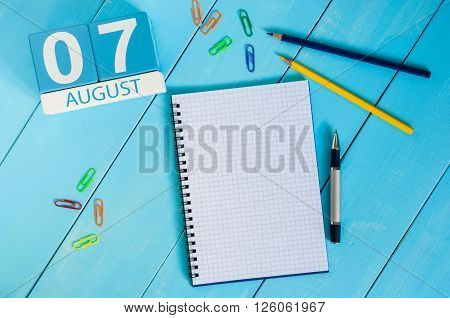 August 7th. Image of august 7 wooden color calendar on blue background. Summer day. Empty space for text.