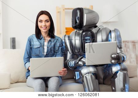 Adore reality.  Delighted attractive positive girl sitting on the couch and using laptop while robot looking at her