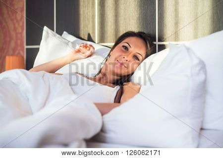 portrait of woman waking up, resting  in bed early morning.