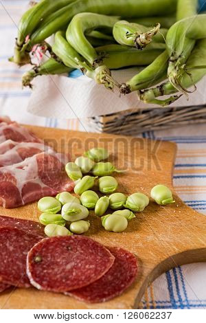 Chopping board with ham salami and broad bean
