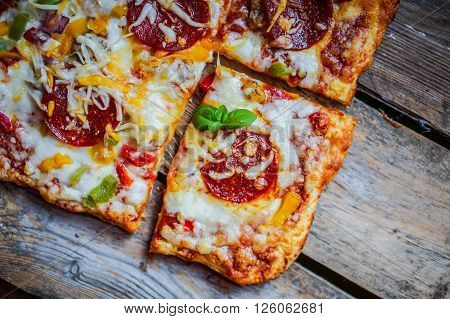Square Pepperoni Pizza On Rustic Wooden Background