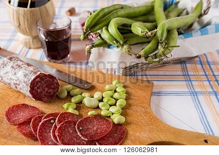 Chopping board with salami broad bean and a glass of red wine