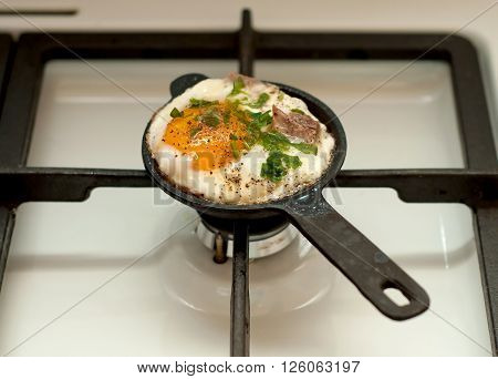 Fried egg in small pan cooking on gas-stove