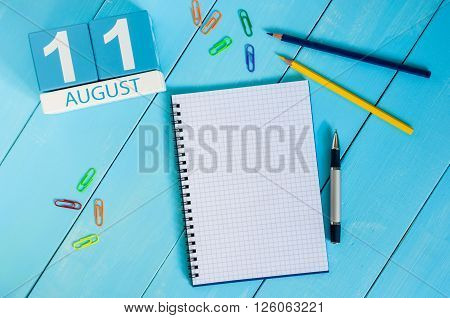 August 11th. Image of august 11 wooden color calendar on blue background. Summer day. Empty space for text.