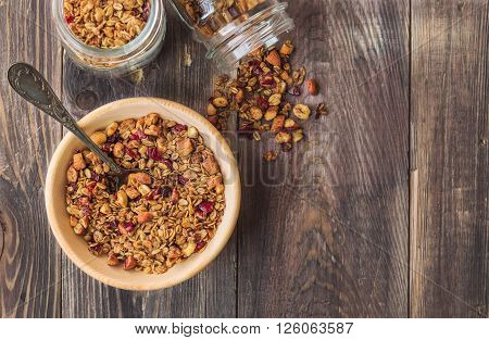 Homemade granola muesli with nuts and dried cranberries in wooden bowl on rustic wooden background. Healthy breakfast. Top view. ** Note: Soft Focus at 100%, best at smaller sizes