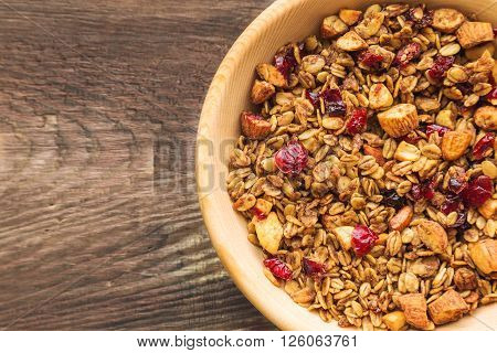 Homemade granola muesli with nuts and dried cranberries in wooden bowl on rustic wooden background. Healthy breakfast. Top view.