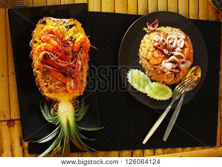 hai food restaurant stuffed with rise shrimps prawn raisin fruit pineapple and seafood octopus squid rice close up photo on the table